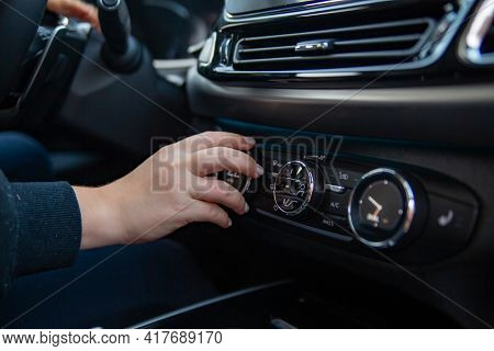 Woman's Hand Switches The Air Conditioning In The Car. Driver Turning On Car Air Conditioning System