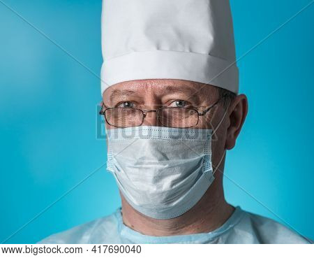 Portrait Of A Middle-aged Experienced Doctor In Medical Clothing And A Mask, Wearing Glasses. Close-