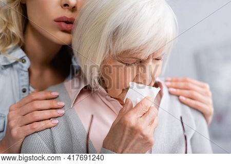 Senior Woman With Napkin Crying Near Daughter.