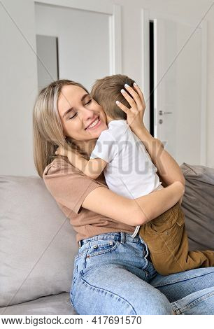 Happy Young Mum Hugging Kid Son Relaxing On Sofa At Home. Cute Toddler Boy And Smiling Mother Bondin