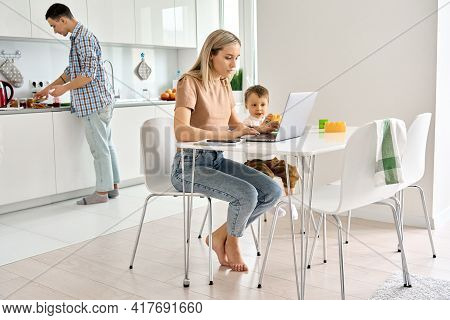 Busy Young Mother Working From Home Office Using Laptop Computer Sitting At Kitchen Table With Cute