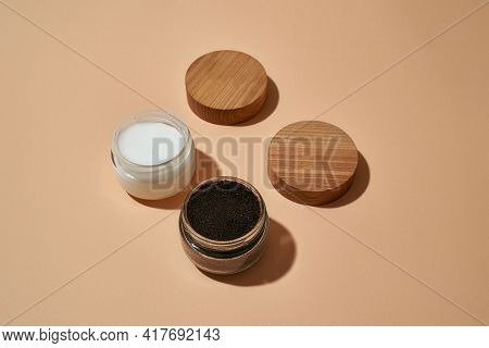 Coffee Scrub And Cosmetological Cream In Open Round Jars Next To Wooden Caps On Light Orange Backgro