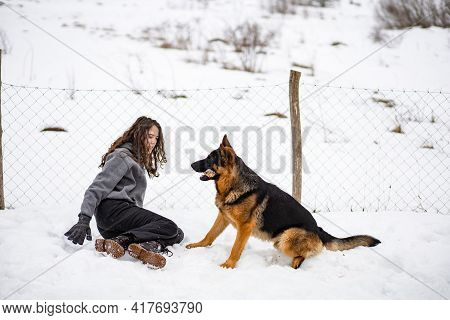 Young Brunette Girl Playing With Her German Shepherd Dog. Wintertime