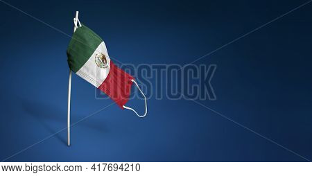 Mexico Mask On Dark Blue Background. Waving Flag Of Mexico Painted On Medical Mask On Pole. Concept