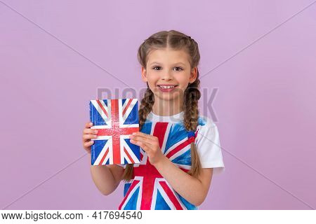 A Little Girl Holds An English Textbook In Her Hands.