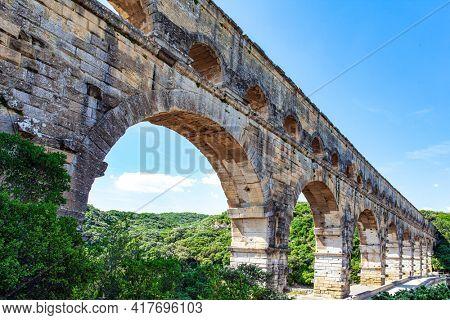 Interesting trip to France. The shallow Gardon River. The Pont du Gard is the tallest Roman aqueduct. The aqueduct  Pont du Gard is a three-tiered arcade of yellow-pinkish limestone.