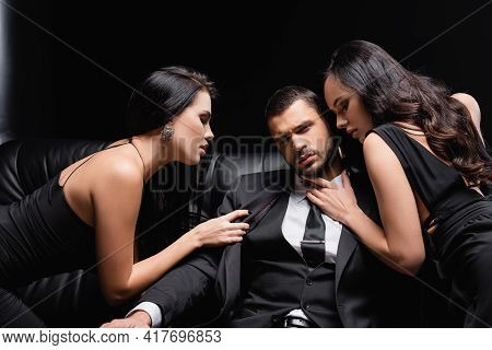 Successful Businessman Near Passionate Women Seducing Him On Leather Couch On Black.
