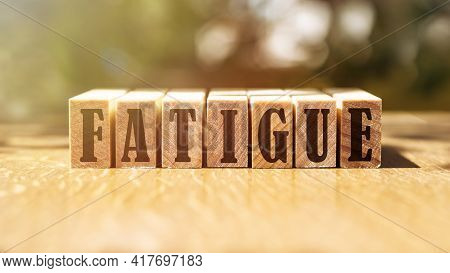 Word Fatigue Made With Building Wooden Blocks On Table In Sunlight