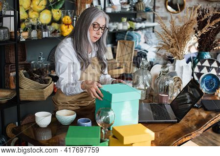 Attractive Aged Woman In Eyeglasses And Apron Doing Inventory At Decor Store. Competent Saleswoman R