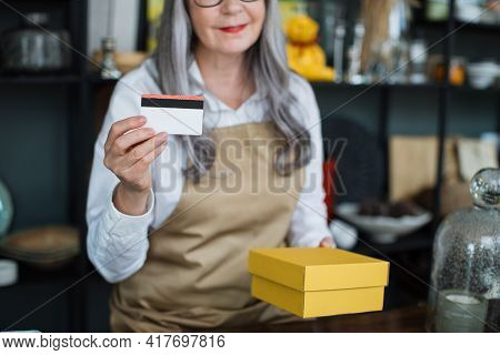 Close Up Of Experienced Mature Saleswoman Holding Credit Card In One Hand And Yellow Paper Box In An
