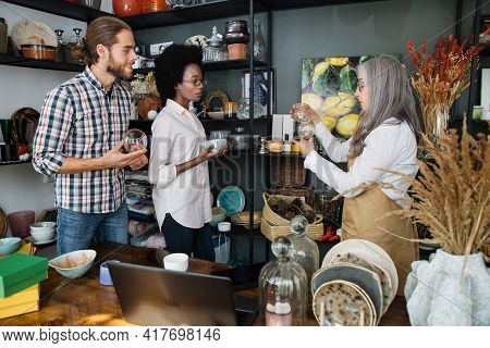 Caucasian Man And African Woman Listening Carefully Mature Saleswoman While Choosing Exclusive Produ