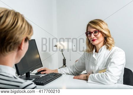 Blonde Female Physician Doctor In Her Office With Pedi-scoliometer On A Table. Portrait Of Friendly