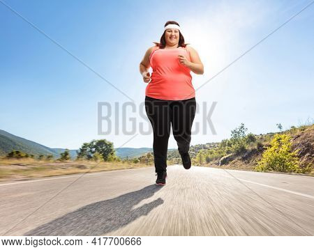 Full length portrait of an overweight woman jogging outdoors on an open road