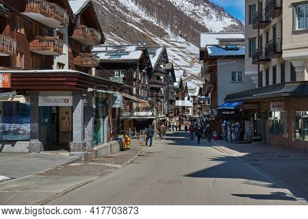 Zermatt, Switzerland - Circa 2021: People passing by on the streets of well-know mountain swiss resort town Zermatt. Winter scene with people passing by