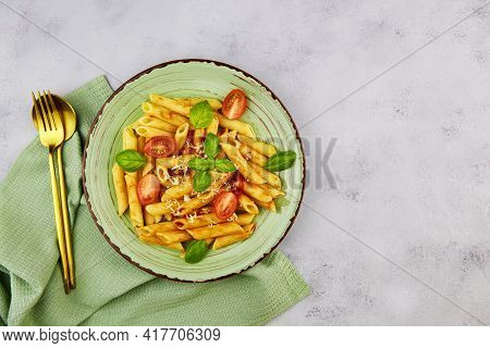 Pasta Penne With Tomatoes, Cheese And Basil On Grey Background. Top View With Copy Space.