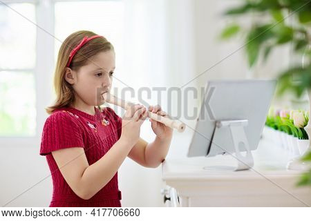 Child Playing Flute. Remote Learning From Home. Arts For Kid. Little Girl With Musical Instrument. V