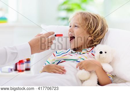 Sick Little Boy With Medicine. Mother Checking Fever Of Ill Child In Bed. Unwell Kid With Chamber In