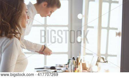 Make-up artist applying white eyeshadow in the corner of model's eye and holding a shell with eyeshadow on background