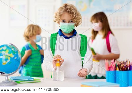 Kids In Face Mask In School Class With Hand Sanitizer. Sanitizing In School. Student Child In Corona