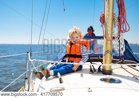 Kids Sail On Yacht In Sea. Child Sailing On Boat. Little Boy In Safe Life Jackets Travel On Ocean Sh