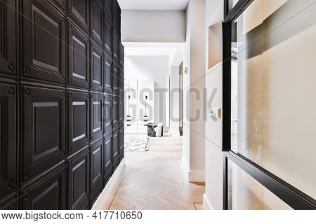 Narrow Hallway With Black Wall Panels Leading To Light Room In Contemporary Flat