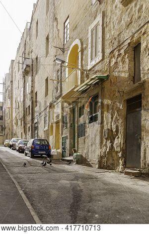 Valletta, Malta - February 20, 2010. Cars Parked On Ancient Narrow Street With Old Fashioned Balconi