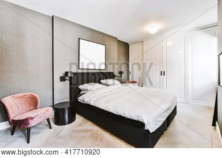 Comfortable Bed With Duvet And Pillows Located Near Chair And Wall With Framed Painting Against Ward