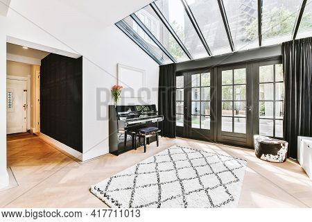 Piano And Carpet Placed In Light Hall Of Modern Cottage With Glass Door And Ceiling Window