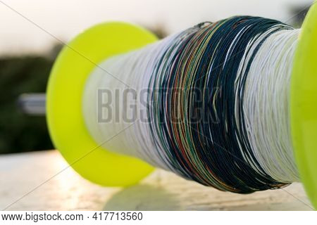 A Close Up Shot Of Kite Spool With Thread And Colorful Manja. India