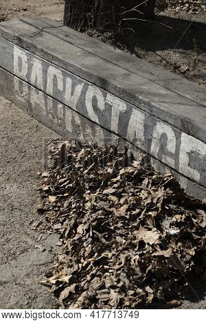 Vertical Shot With Diagonal White Inscription 'backstage' On A Street Bench Next To Fallen Leaves