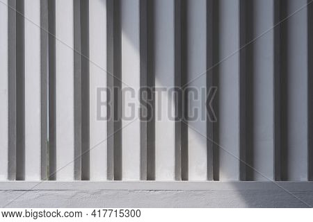 White Wooden Sunshade Battens On Cement Wall With Sunlight And Shadow On Surface