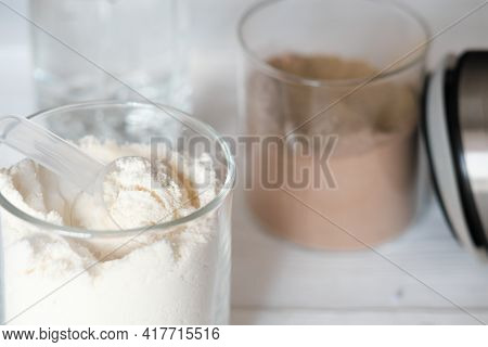 Close Up View Of Whey Protein In Jars With Protein Powder. Chocolate And Vanilla Flavored Supplement