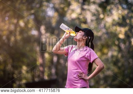 Close-up Of Beautiful Asian Woman Sport Athletes Drinking Water With Electrolytes After Exercise. As