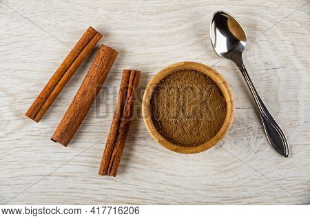 Cinnamon Sticks And Bamboo Bowl With Ground Cinnamon, Spoon On Light Wooden Table. Top View