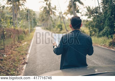 A Man With Backpack Hiking Read A Map In Front Of Car On The Road In Forest. Backpack Travel Concept