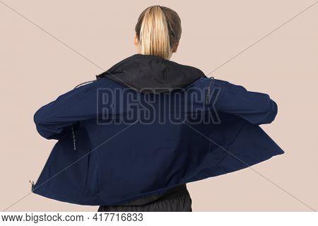 Blonde woman in windbreaker jacket for sportswear fashion photoshoot rear view
