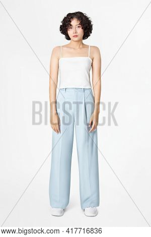 Woman in white tank top and blue loose pants minimal fashion