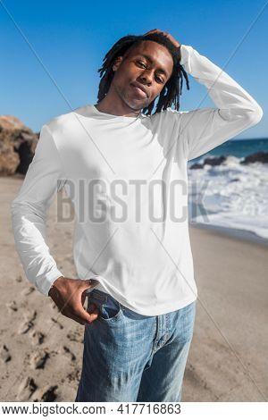 Man in white long sleeve tee walking on the beach