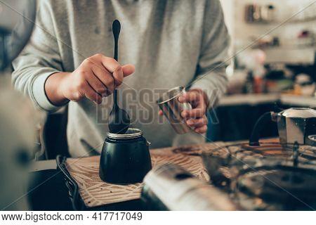Barista Measure Coffee Powder And Brewing Black Moka Coffee Using Moka Coffee Maker.