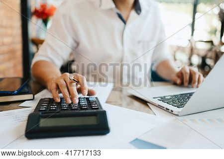 Businessman Hand Using Calculator For Calculate About Cost, Tax Or Budget On The Table In Office.