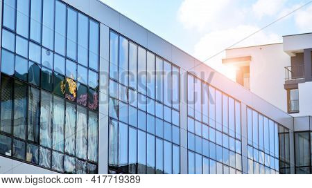 Blue Sky Reflection In Glass Facade Of Building. View Of Office Building Windows Close Up With Sunri
