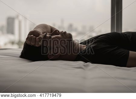 Hand On Asian Man Forehead When Feels Worry On Bed With City Background. Stay Home, Depression And L