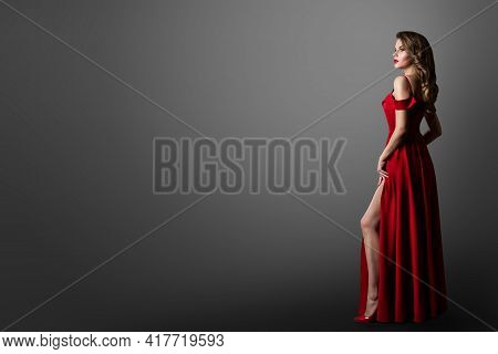 Fashion Woman In Long Red Dress. Model Showing Leg In Evening Silk Slit Gown. Side Profile View. Bla