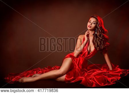Sexy Woman Red Dress Fashion. Sensual Model Lying In Slit Gown. Evening Make Up And Curly Wavy Hairs