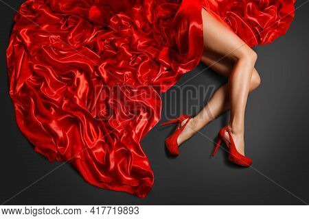 Woman Shoe High Heels Fashion. Model In Red Shoe Red Skirt Dress Lying Over Silk Fabric On Black Bac
