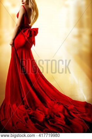 Model Red Dress, Fashion Blonde Woman In Long Evening Gown Back Side View. Yellow Lighting Backgroun