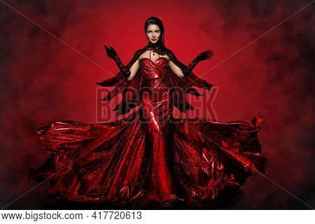 Beautiful Halloween Witch In Red Dress, Gloves And Cape, Gothic Fashion Girl Raised Open Arms, Makin