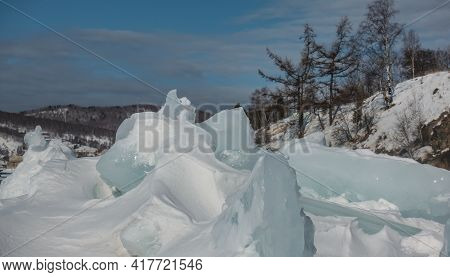 Bizarre Ice Hummocks, Covered With Snow On A Frozen Lake. The Background Is Mountains, Bare Deciduou