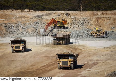Large Yellow Trucks Used In A Modern Mine In Western Australia. A Bulldozer Moves Rock Towards The D