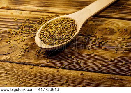 Fenugreek Seeds In Wooden Spoon On Wooden Table